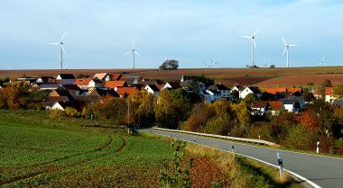 Rooftop solar panels and wind farm. Photo by GLSystem, Wikimedia Commons.