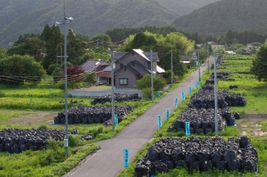 Piles of radiated soil lay along the side of a road in a deserted town near the destroyed Fukushima Daiichi nuclear power plant on June 22, 2015 (Keystone)