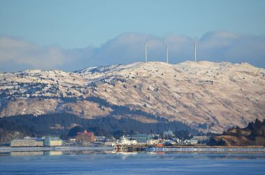 Coast Guard base Kodiak is seen across Women's Bay. Atop Pillar Mountain, beyond the base, are three wind turbines operated by Kodiak Electric Association. Photo by James Brooks. CC BY 2.0.