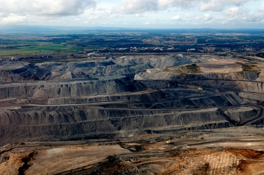 Open pit coal mine in green countryside.