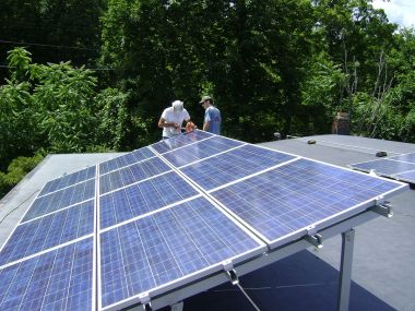 Two workers installing a tilt-up photovoltaic array on a roof near Poughkeepsie, NY. Photo by Lucas Braun. CC BY-SA 3.0. Wikimedia Commons.