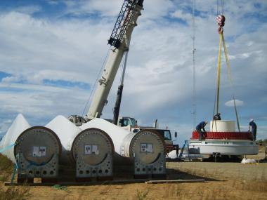 Alaska Environmental Power workers and contractors prepare to hoist the hub of a rotor and the three large blades to a hub. Photo: Tim Ellis/KUAC