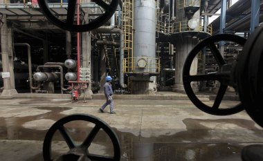 A worker walks past oil pipes at a refinery in Wuhan, Hubei province in this March 23, 2012 file photo. China is expected to report commodities output data on November 11, 2015.  REUTERS/Stringer/FilesTHE ASIA FILE - NOV 11 2015