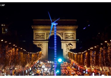 A power-generating wind turbine is seen on the Champs Elysees avenue with the Arc de Triomphe in background as part of COP21. - AP