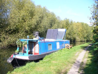 Solar Power on the Grand Union Canal. This narrowboat has been modernized and its two solar panels were collecting rays from a cloudless Hertfordshire sky. Photo by Colin Smith. CC BY-SA 2.0 Generic. Wikimedia Commons.