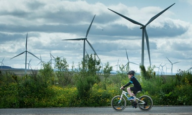 A child cycles past an onshore windfarm. Photograph: Danny Lawson/PA
