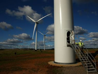 A Vestas service technician walks up the stairs to the door at the base of a wind turbine at the Taralga Wind Farm. (Photo: Mark Kolbe, Getty Images)