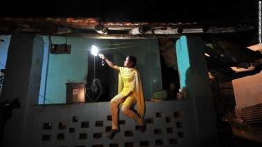A woman turns on a solar-powered light at her home near Mumbai.