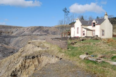 Abandoned farmhouse on the edge open pit mine. Photo by Robert Guthrie. CC BY-SA 2.0. Wikimedia Commons.