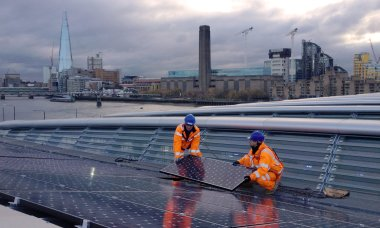 Solar panels are installed on Blackfriars station with an old coal-power station in the background. Photograph: Courtesy Solar Trade Association