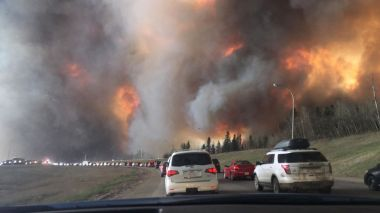 Cars heading toward flames they must pass to leave Fort McMurray. Photo by DarrenRD. CC BY-SA International. Wikimedia Commons.