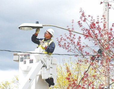 Dan Reed of Siemens installs a LED street light on Carroll Street in Manchester last year. (Union Leader File)