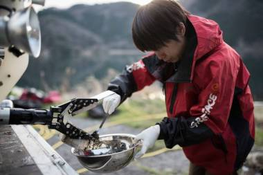 A Greenpeace Japan member removes sediment samples from a remotely operated grabber at Lake Biwa. | © Christian Åslund / Greenpeace