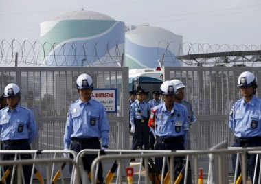 Police officers and security personnel stand guard at an entrance of Kyushu Electric Power's Sendai nuclear power station, during a protest. Photo by Issei Kato / Reuters.