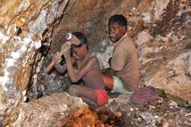 Seven-year-old Karulal works with his father in a mica mine. Photograph: Peter Bengtsen