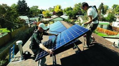 Namaste Solar employees put solar panels on a house in Denver. Kathleen Lavine | Denver Business Journal