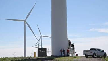 MidAmerican personnel examine a wind turbine