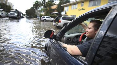 Sandy Garcia sits in her vehicle on a flooded street in Fort Lauderdale. (Joe Raedle / Getty Images)