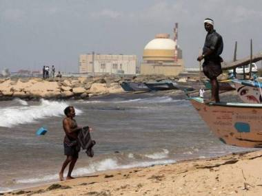 A fisherman stands on his boat on a beach  near Kudankulam nuclear plant. (Photo: Reuters)