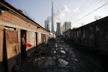 A migrant worker steps out of his accommodation in an area next to a coal power plant in Beijing on a smog-free day. (Reuters / Damir Sagolj)